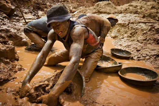 Gold miner scoops mud while digging an open pit in northeastern Congo